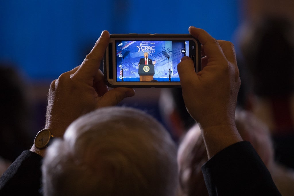 A CPAC attendee captures a presidential moment. (Photo: Jeff Malet for The Daily Signal)