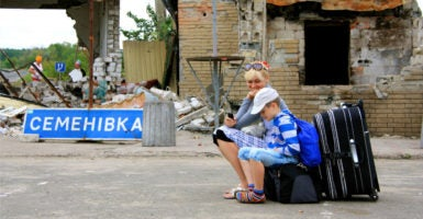 A woman and her child wait for a ride out of Sloviansk in August 2014, only weeks after a battle to liberate the city. (Photo: Nolan Peterson/The Daily Signal)