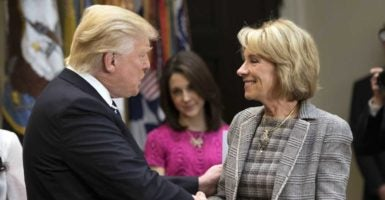 President Donald Trump shakes hands with his Education Secretary Betsy DeVos. (Photo: Kevin Dietsch/UPI/Newscom)