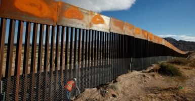 A worker inspects a section of the U.S.-Mexico border. (Photo: Jose Luis Gonzalez / Reuters)