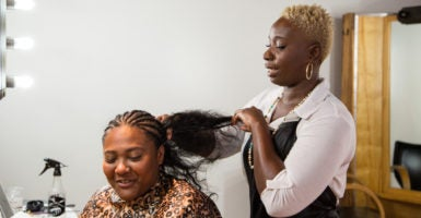 In a new report, the Institute for Justice found licensing laws for hair braiders like Aicheria Bell, pictured, did little to improve public health and safety. Iowa, where Bell lives, recently passed legislation eliminating licensing requirements for hair braiders. (Photo: Institute for Justice)