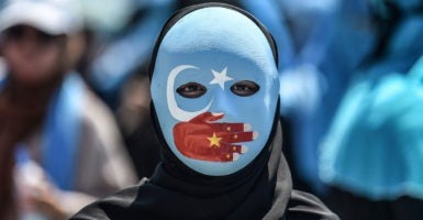 "At least 1 million Uighurs—a Chinese ethnic-Muslim minority—have been sent to ""political re-education camps"" to erase their identity and assimilate them into the Han majority for the purposes of conforming their religious beliefs to the party's beliefs. Pictured: A demonstrator attends a protest to denounce China's treatment of ethnic Uighur Muslims during a deadly riot in July 2009 in Urumqi, in front of the Chinese consulate in Istanbul, on July 5, 2018. - (Photo: Ozan Kose/AFP/Getty Images)"