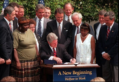 August 22, 1996 Surrounded by bipartisan members of Congress, Governors, administrative officials and former welfare recipients, President Bill Clinton signs welfare reform legislation Thursday at the White House. Known as the Personal Responsibility and Work Opportunity Reconciliation Act of 1996, the bill ends 60 years of guaranteed monetary assistance to the poor. The three former welfare recipients are (from left, all women, standing around the President): Lillie Harden from Arkansas, Penelope Howard from Deleware and Janet Ferrel from West Virginia.