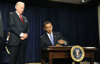 U.S. President Barack Obama signs executive order on Executive Branch ethics as Vice President Joe Biden watches on during a signing ceremony in the Eisenhower Executive Office Building in Washington on January 21, 2009. (UPI Photo/Kevin Dietsch)
