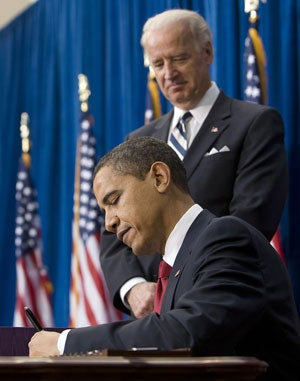 US Vice President Joe Biden (R) stands with US President Barack Obama (C) as he signs the American Recovery and Reinvestment Act at the Denver Museum of Nature and Science in Denver, Colorado, on February 17, 2009.