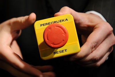 "An assistant shows the block with a red button marked ""reset"" in English and ""overload"" in Russian that US Secretary of State Hillary Clinton handed to Russian Foreign Minister Sergei Lavrov during a meeting on March 6, 2009 in Geneva."