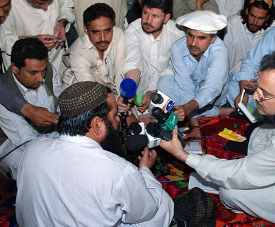 "In this picture taken on May 24, 2008, Pakistani Taliban commander Baitullah Mehsud (C) speaks to media representatives at his stronghold in the tribal district of South Waziristan near the Afghan border. Top Pakistani Taliban warlord Mehsud on May 24 said jihad, or holy war, would continue in Afghanistan, despite peace negotiations between the militants and Islamabad. ""Islam does not recognise boundaries and jihad in Afghanistan will continue,"" he said"