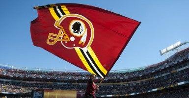A cheerleader waves a Washington Redskins flag. (Photo: Kevin Dietsch/UPI/Newscom)