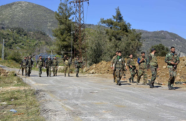 Pro-regime soldiers are seen marching on a road in the village of Kasab, in the northwestern province of Latakia, on March 27, 2014. Photo: FP PHOTO/AFP/Getty Images