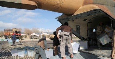 An Afghan election worker unloads ballot boxes from a military helicopter for the counting in Ghanzi province in eastern Afghanistan on April 9, 2014. (Photo: Xinhua/Sipa USA/Newscom)