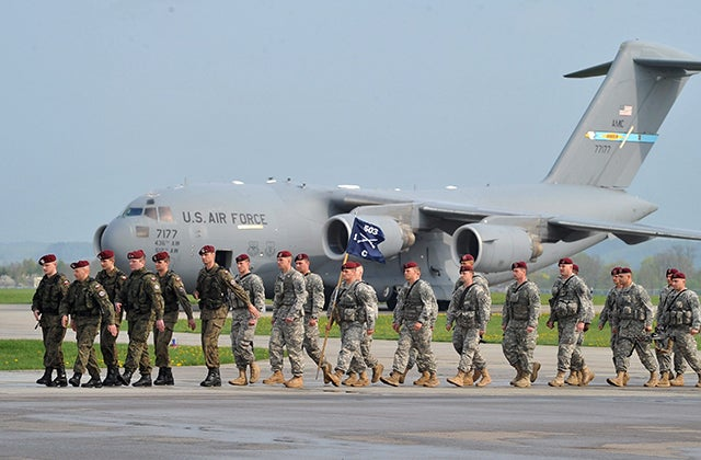Polish soldiers (L) accompany US Airborne soldiers upon their arrival at the military airport in Swidwin, northern Poland, 23 April 2014. An US Army company of about 150 soldiers from the 173rd Airborne Brigade Combat Team based in Vicenza, Italy, came for military exercises in Poland due to the political situation in Ukraine. The exercises, involving some 600 troops, also take place in Estonia, Latvia and Lithuania, and is scheduled to last for about a month. (Photo: MARCIN BIELECKI/EPA/Newscom)