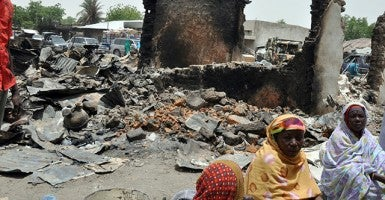 Women sit at Gamboru central market burnt by suspected Boko Haram. (Photo: Newscom/Getty Images)