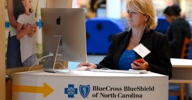 Kelli Tremblay, an authorized agent with BlueCross BlueShield of North Carolina, works a station at Concord Mills on Tuesday, October 1, 2013, during the first day of enrollment for Obamacare. (Photo: (Jeff Siner/MCT/Newscom)