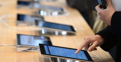 A customer uses a tablet while holding a smartphone. (Photo: Hertzog/AFP/Newscom)