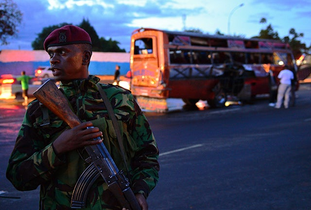 A Kenyan policeman stands in front of the wreckage of a bus at the site of a bomb blast in Nairobi on May 4, 2014. (Photo: CARL DE SOUZA/AFP/Getty Images/Newscom)
