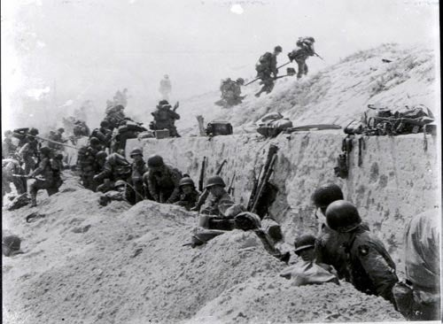 Soldiers of the 8th Infantry Regiment, 4th Infantry Division, move over a seawall on Utah Beach. (Photo: US Army/Flickr)