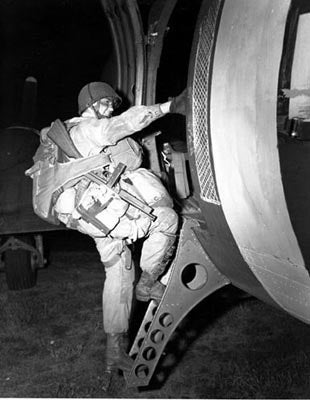 A paratrooper boards an airplane that will drop him over the coast of Normandy for the Allied Invasion of Europe, D-Day, June 6, 1944. Soldiers of the 82nd and 101st Airborne Divisions parachuted behind enemy lines during the night, while fellow Soldiers assaulted Normandy beaches at dawn. (Photo: US Army/Flickr)