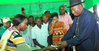 Nigerian incumbent President Goodluck Jonathan receives his voting credentials at a polling station. (Photo: George Esiri/EPA/Newscom)