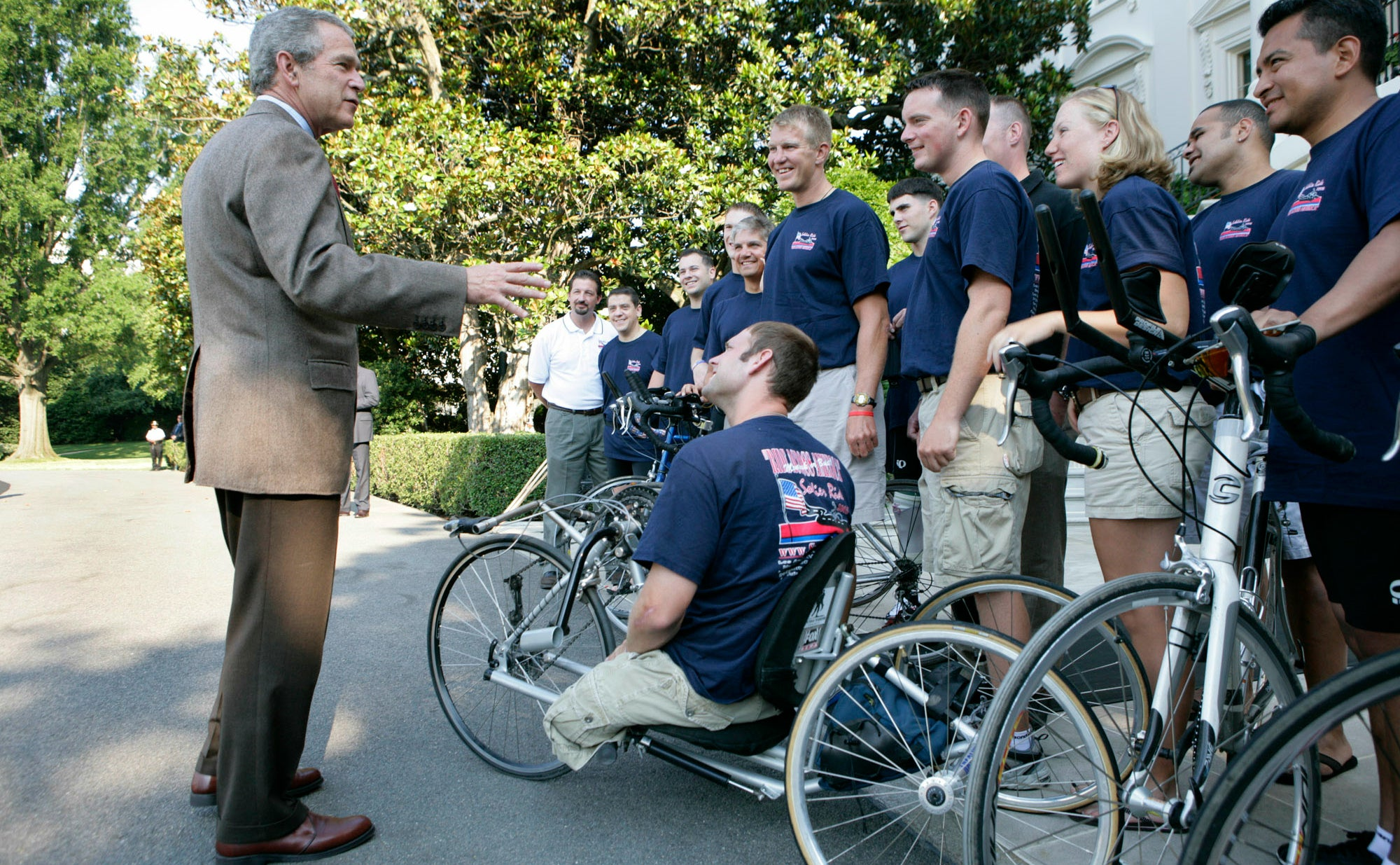 George W. Bush speaks with members of Soldier Ride 2005 National Tour Team. Soldier Ride 2005, comprised of wounded service members, is a 4,200-mile, cross-country bike ride to raise money and support to help prepare wounded soldiers for long-term rehabilitation. (Photo: Eric Draper/White House/ZUMA Press/Newscom)