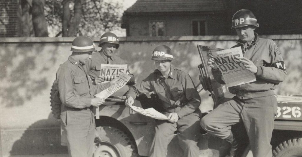US military policemen read about the German surrender in the newspaper 'Stars and Stripes.' (Photo: US Army/Public Domain)