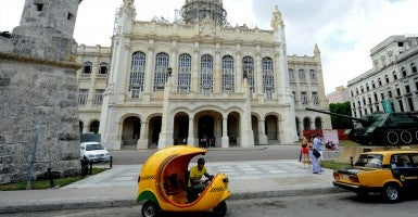 In Havana, Cuba, a coco taxi, a bright yellow egg-shaped rickshaw-type vehicle, is seen in front of the Museum of the Revolution (Photo: Paul Hennessy/Polaris/Newscom)