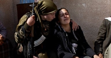Kurdish fighter Zozan, 20 years old, consoles the relative of her comrade killed during the clashes against Islamic State group yihadists. (Photo: JM Lopez/Sipa USA/Newscom)