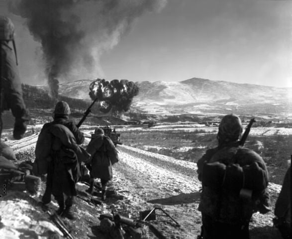 Marines watch F4U Corsairs drop napalm on Chinese positions. (Photo: Wikimedia)