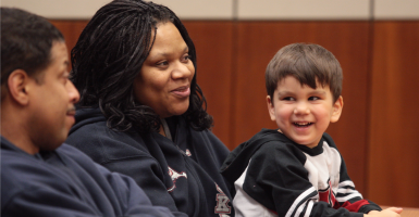 In this 2009 photo, then-two-year old Mahkel smiles while sitting with his adoptive parents Enrique and Pamela Santos during the adoption court proceedings. (Photo: Eric Engman/ZUMApress/Newscom)
