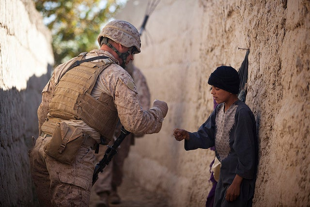 "U.S. Marine Lance Cpl. Dominic Evola, a 29-year-old rifleman with Jump Platoon, Headquarters and Service Company, 3rd Battalion, 3rd Marine Regiment, from Medford, N.J., greets an Afghan boy by ""pounding fists."" (Photo: Cpl. Reece Lodder)"