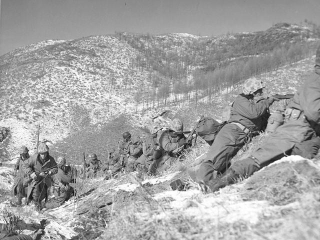 Marines under the cover of a large boulder engaging the Chinese. (Photo: Wikimedia)