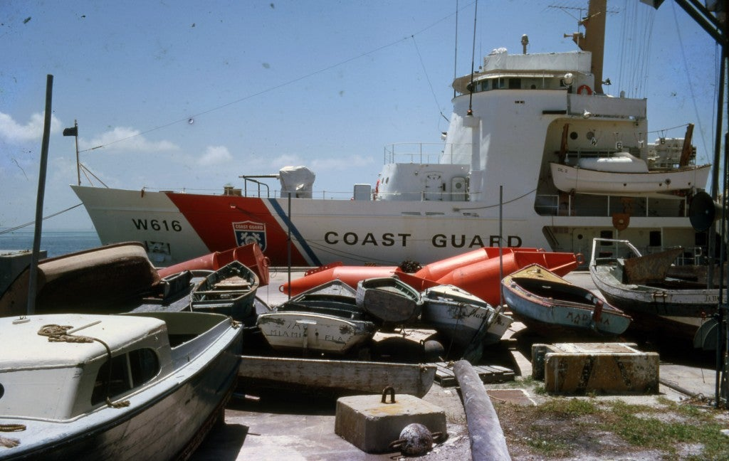 Discarded refugee boats piled up on a Miami pier by the Coast Guard in May 1980. (Photo: Florida Keys Public Library, Raymond Blazevic/CC By 2.0)