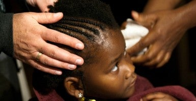 "Excessive regulations pushed by the left hurt a woman trying to run her own hair-braiding business. (Photo: ""Hair Braiding Lourdie Qiqi December 20, 20102"" is copyright by Steven Depolo and made available under a Attribution-NoDerivs 2.0 Generic license via Flickr. Link: https://goo.gl/pfs7nR)"