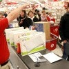 Holiday shoppers queue to make their purchases after braving the crowds in Target. (Phot