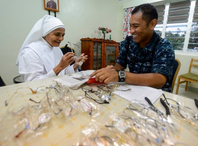 U.S. Navy Hospital Corpsman Herber Gutierrez prescribes a pair of reading glasses to Sister Margaret Du Coeur Immaculee of Little Sisters of the Poor nursing home while visiting to donate medical supplies and bedding during Pacific Partnership 2013.