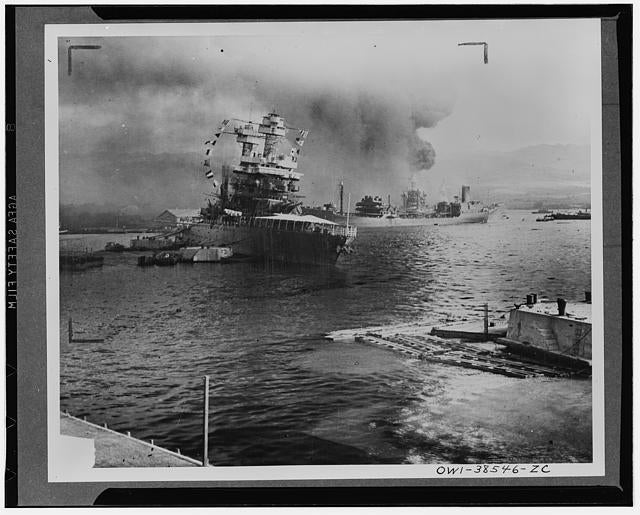 The U.S.S. Neosho, navy oil tanker, cautiously backs away from her berth (right center) in a successful effort to escape the Japanese attack on Pearl Harbor, Dec. 7, 1941. At left the battleship U.S.S. California lists after aerial blows. Other crippled warships and part of the hull of the capsized U.S.S. Oklahoma may be seen in the background. The Neosho was later sunk in the Coral Sea. (Photo: Library of Congress Prints and Photographs)