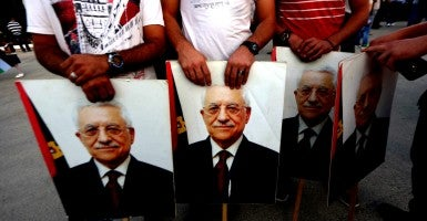 Palestinian hold pictures of president Mahmoud Abbas as they greet him upon his arrival from New York on October 2, 2015 where he attended a ceremony to mark the raising of the Palestinian flag at the United Nations headquarters. (Photo: Shadi Hatem/ZUMA Press/Newscom/Edited:Daily Signal)