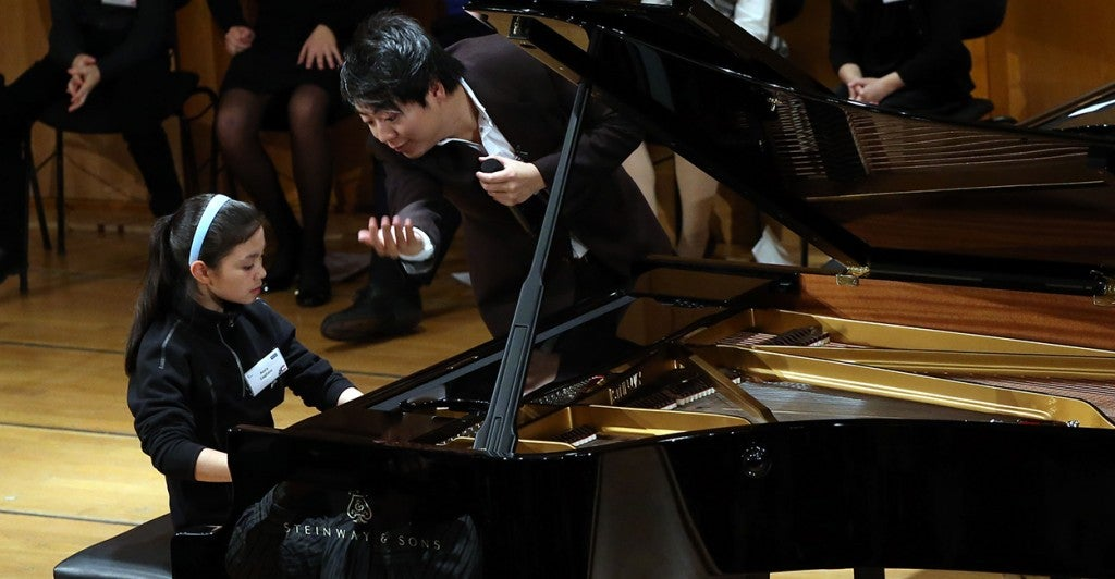 Avery receives lessons from starpianist Lang Lang during the Junior Music Camp in Munich. (Photo: Newscom)