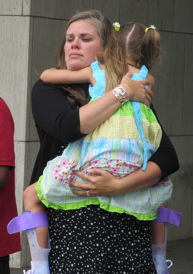 Carrie Pratt holds daughter Dagen, then 6, at a news conference last August outside HHS headquarters.  (Photo: Angela Bradbery/Public Citizen)