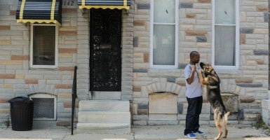 Sandtown-Winchester resident Doni Glover kisses his dog Pharaoh outside his home on May 5, 2015 in Baltimore, Md. (Photo: Jessica Koscielniak/TNS/Newscom)