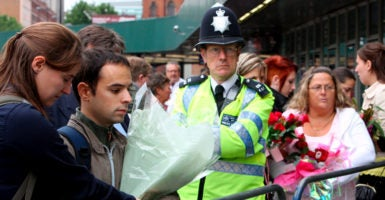 Mourners remember victims of the July 7, 2005, bombings of London's public transport network by Islamist terrorists. By law, Britons who are part of public institutions serving youth also must protect them from going the extremist route. (Photo: Andy Rain/EPA /Newscom)