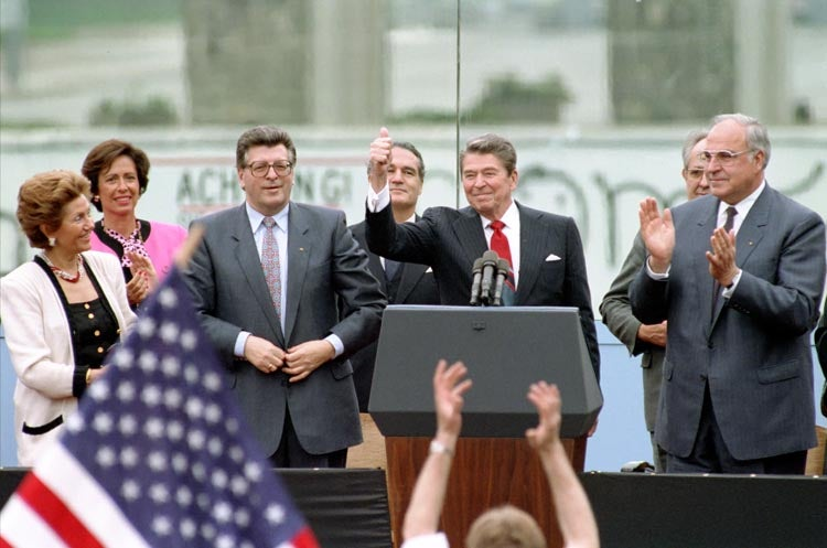 Reagan at podium with a thumbs up with German Chancellor Helmut Kohl, German political leader Philipp Jenninger and his wife. (Photo: Ronald Reagan Library)