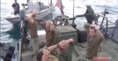 American sailors surrender in a blurry clip released by state-controlled Iranian media. One of their captors can be seen at upper left. (Photo: Newscom)