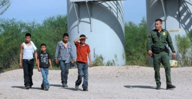 A U.S. Border Patrol agent escorts a group of Central American immigrants following their surrender after illegally entering the country from Mexico. (Photo: Paul Hennessy/Polaris/Newscom)