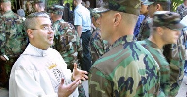 Army Chaplain, Father Joseph Angotti, talks with a soldier following mass at the Regimental Chapel on Sand Hill in Fort Benning, Ga.  (Photo: ROBIN TRIMARCHI/KRT/Newscom)