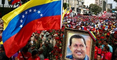 Supporters of Venezuela's President Nicolas Maduro hold a portrait of Venezuela's late president Hugo Chavez during a rally against imperialism, in Caracas March 15, 2015 (Photo: Carlos Garcia Rawlins/REUTERS/Newscom)