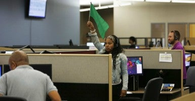 A customer service agent at Covered California's Concord call center waves a flag for technical assistance during the opening day of enrollment. (Stephen Lam/Reuters/Newscom)