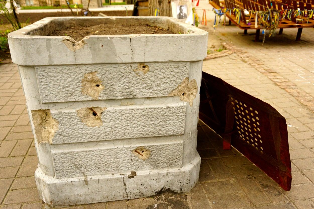 Bullet holes pockmark a planter on Institutskaya Street in central Kyiv.