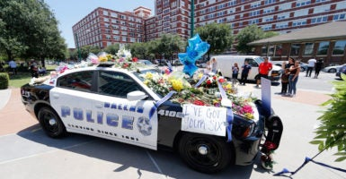 Flowers cover a Dallas Police Department cruiser after five  officers were killed by a sniper during a protest. (Photo: Erick S. Lesser /EPA/Newscom)