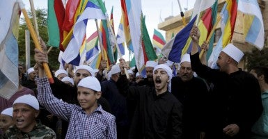 Members of the Druze community wave flags during a protest in the Druze village of Majdal Shams on the Golan Heights, June 15, 2015. (Photo: Ammar Awad/Reuters/Newscom)