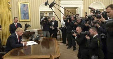 President Donald Trump signs an executive order directing federal agencies to ease the burden of Obamacare in front of the White House press pool. (Photo: Kevin Dietsch/UPI /Newscom)